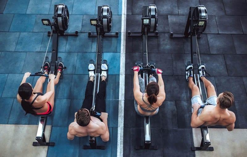 mujeres y hombres entrenando con maquinas de remo