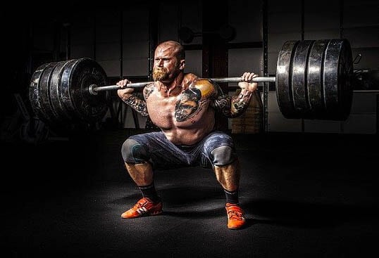 hombre haltera levantando barra con pesas de disco